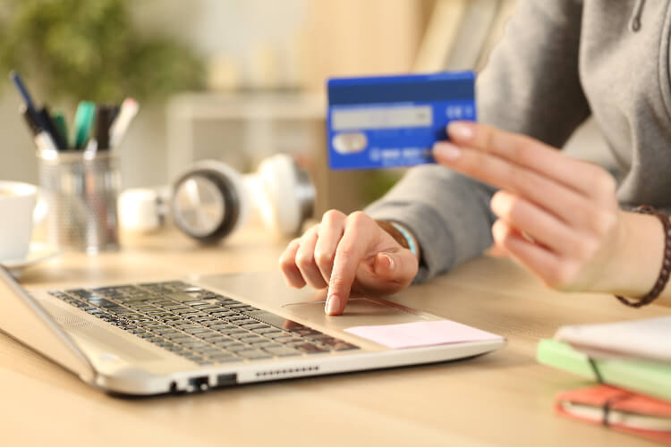 person using credit card on computer
