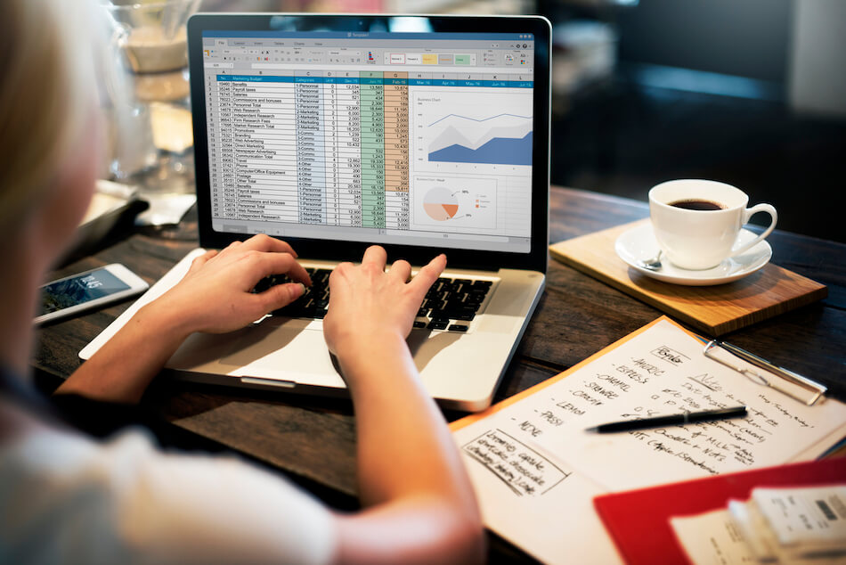 woman working on spreadsheet with coffee